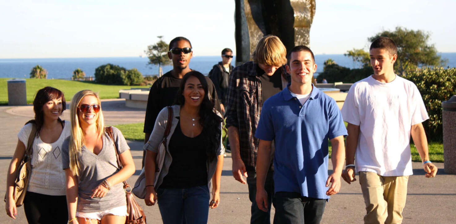 a group of international university students walking near the beach and having a conversation about their USA education