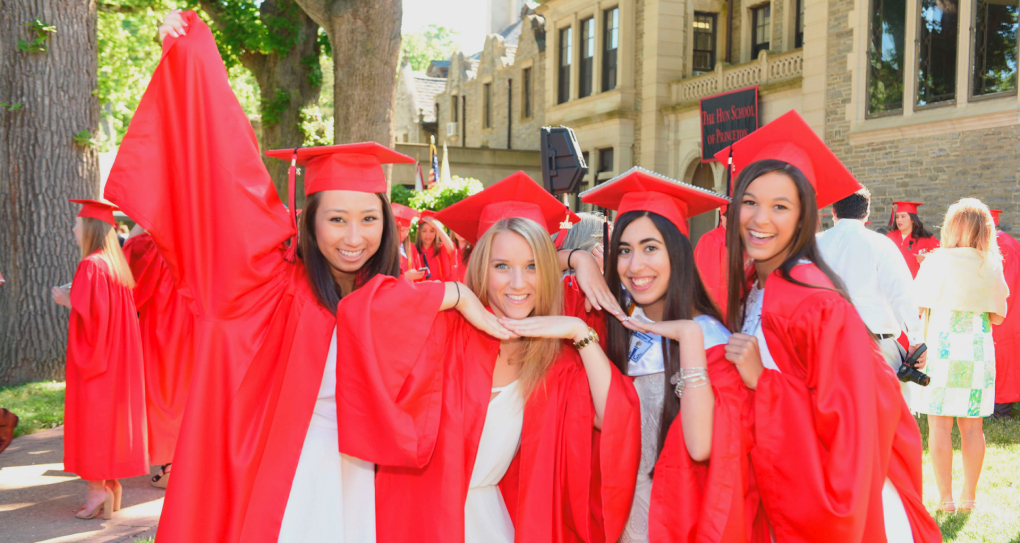 four Cogito female teenagers in red caps and gowns smiling and standing in front of a school building