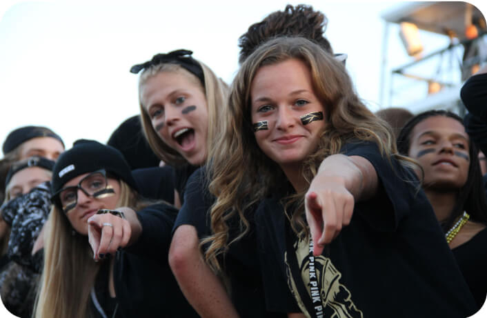 a group of high school students wear face makeup and matching black outfits for a football game
