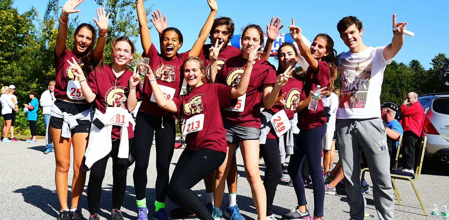 A large group of high school students from the USA take a group picture at a half-marathon race event