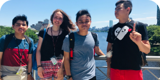 four young cogito high school students smile for a group photo in front of the charles river in the city of boston