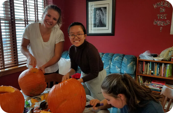 three cogito students sit together and carve fun designs into pumpkins at a host-family stay during our summer program