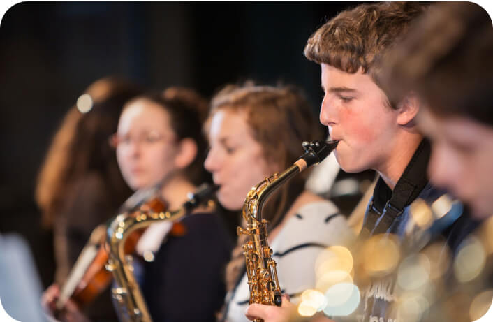 a young male student plays the saxophone during a high school concert for the arts, a tradition at our summer program